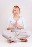 den blonda meditationen poserar kvinnayogabarn Arkivfoton