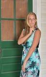 Den blonda modemodellen poserar nära stängt med fönsterluckor hus fotografering för bildbyråer