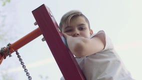 Den blonda pojken klättrade på en gunga och blickar in i kameran från vertikalt Aktiv livsstil, bekymmersl?s barndom stock video