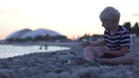 Den blonda pojken sitter på havskusten och kaststenarna in i vattnet stock video