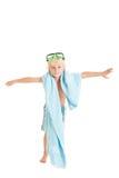 Den blonda pojken som ha på sig simningkort stavelse, och simning maskerar med en blåtthandduk. Arkivfoton