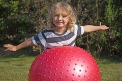 Den blonda pojken spelar med den gymnastiska bollen Arkivbild