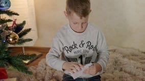 Den blonda pojken under julträd sätter en bokstav till jultomten i ett kuvert arkivfilmer
