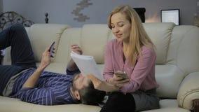 Den blonda studenten läser hennes anmärkningar, förbereder sig att ta examina på en soffa hemma stock video