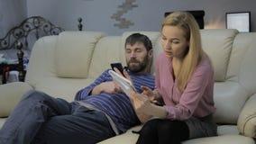 Den blonda studenten läser hennes anmärkningar och hennes pojkvän som sitter på soffan och brukssmartphones lager videofilmer