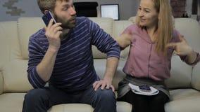 Den blonda studenten läser hennes anmärkningar och hennes pojkvän som sitter på soffan och brukssmartphones arkivfilmer