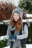 Den blonda tonåringflickan som gör en kasta snöboll i snöig, parkerar Arkivbild