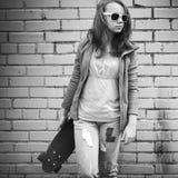 Den blonda tonårs- flickan i jeans och solglasögon rymmer skateboarden Royaltyfri Fotografi