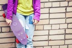 Den blonda tonårs- flickan i jeans rymmer skateboarden Fotografering för Bildbyråer