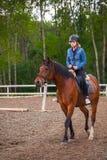 Den blonda tonårs- flickan rider den bruna hästen arkivfoto
