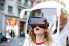 Den blonda unga kvinnan använder VR-hörlurar med mikrofon royaltyfri bild