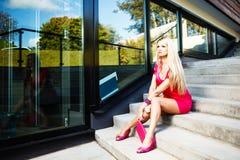 Den blonda unga kvinnan i rosa färger klär att posera nära modern byggnad Royaltyfri Foto