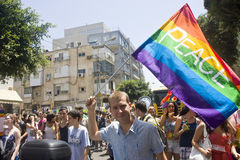 Den blonda ungdommen med fredflaggan på stolthet ståtar TA Arkivfoton