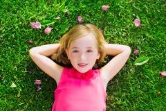 Den blonda ungeflickan som ligger på le antenn för trädgårds- gräs, beskådar Royaltyfri Foto