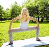 Den blonda verkliga flickan som gör yoga i gräsplan, parkerar, verkligt folk för livsstilen Arkivbild