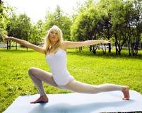 Den blonda verkliga flickan som gör yoga i gräsplan, parkerar, verkligt folk för livsstilen Royaltyfri Foto