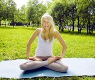Den blonda verkliga flickan som gör yoga i gräsplan, parkerar, verkligt folk för livsstilen Royaltyfria Foton