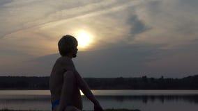 Den blonda yogin sitter i en örnposition på en sjöbank i slo-mo arkivfilmer