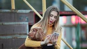 Den blondin- och hund-cockerspanieln spanieln justerar hennes hår som ser reflexionen på smartphoneinternet arkivfilmer