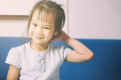Den blyga asiatiska flickan skrapar hennes huvud Royaltyfri Foto
