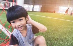 Den blyga pojken sitter bredvid fotbollövningsfält Arkivfoto