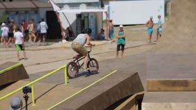 Den Bmx ryttaren rider en cykel och övande trick i BMX-parkera stock video