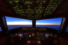 Den Boeing 777 cockpiten som över flyger över det Stillahavs- havet, piloter utförde deras arbete under soluppgång över den  royaltyfria bilder
