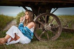 Den Boho hippieflickan med jeans klår upp och den vita klänningen nära släpet Royaltyfri Fotografi