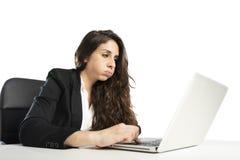 Den borrade kvinnan fnyser i kontoret, medan arbeta på bärbara datorn arkivfoton