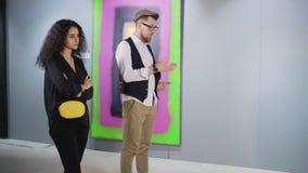 Den borrade mannen och kvinnan står framme av abstraktionbild i galleri stock video