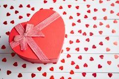 Den boxades gåvan som förlades på hjärta, formade röda paljetter på den vita trätabellen royaltyfri bild