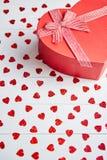 Den boxades gåvan som förlades på hjärta, formade röda paljetter på den vita trätabellen arkivbild