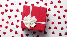 Den boxades gåvan som förlades på hjärta, formade röda paljetter på den vita trätabellen stock video