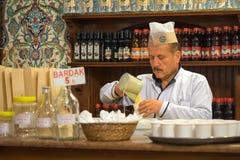 Den Boza säljaren häller drinken i exponeringsglas i ett kafé arkivfoto
