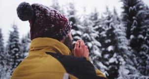 Den bra seende unga grabben i mitt av den snöig skogen beundrar all skönhet runt om drinken någon varm drink från järnkoppen och stock video