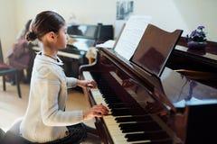 Den bra studenten spelar pianot på en musikskola arkivbild