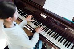 Den bra studenten spelar pianot på en musikskola arkivbilder