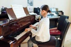 Den bra studenten spelar pianot på musikskolan royaltyfria foton