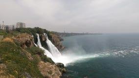 Den branta steniga klippan med en härlig vattenfall som flödar in i havet, i bakgrunden kan du, se husen av staden lager videofilmer