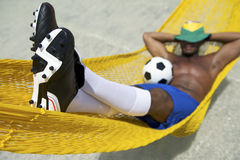 Den brasilianska fotbollspelaren kopplar av med fotboll i strandhängmatta royaltyfri foto