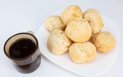Den brasilianska frukosten, ostbröd pao de queijo tjänade som på maträtt på den vita tabellen med kaffe arkivbild