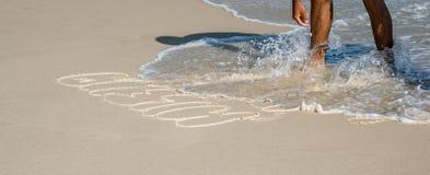 Den brasilianska mannen skrev ner hans namn och namnet av hans älskade kvinna på den Copacabana stranden, Rio de Janeiro royaltyfri foto