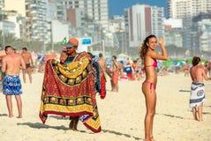 Den brasilianska mannen som säljer pareos, och den härliga sexiga kvinnan i bra form som ser kameran på Copacabana, sätter på lan arkivbild
