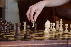 Den breda kantjusterade bilden av en mänsklig hand som flyttar ett schackstycke av ett ljus, pantsätter arkivbild