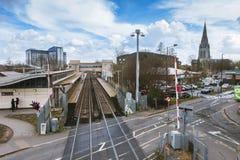 Den breda sikten av den Feltham järnvägsstationen och tornet av dendemolerade `en s för St Catherine kyrktar Arkivfoto