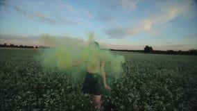 Den breda sikten av den unga attraktiva brunettflickan i kjol med en grön rök bombarderar på fältet Flicka som har roligt skratta arkivfilmer