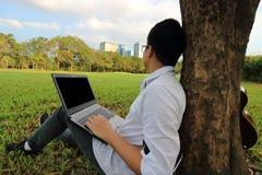 Den breda vinkeln sköt av ung hipsterman mot den tomma skärmen av bärbara datorn och att se stadsbakgrund royaltyfri foto
