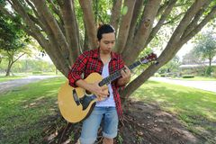 Den breda vinkeln sköt av den unga hipstermannen som spelar musik på den akustiska gitarren i en härlig naturbakgrund Arkivfoto