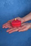 Den brinnande hjärta-stearinljuset på gömma i handflatan background card congratulation invitation Arkivbilder