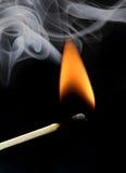 Den brinnande matchsticken, den orange flamman och grå färger röker på Arkivfoton